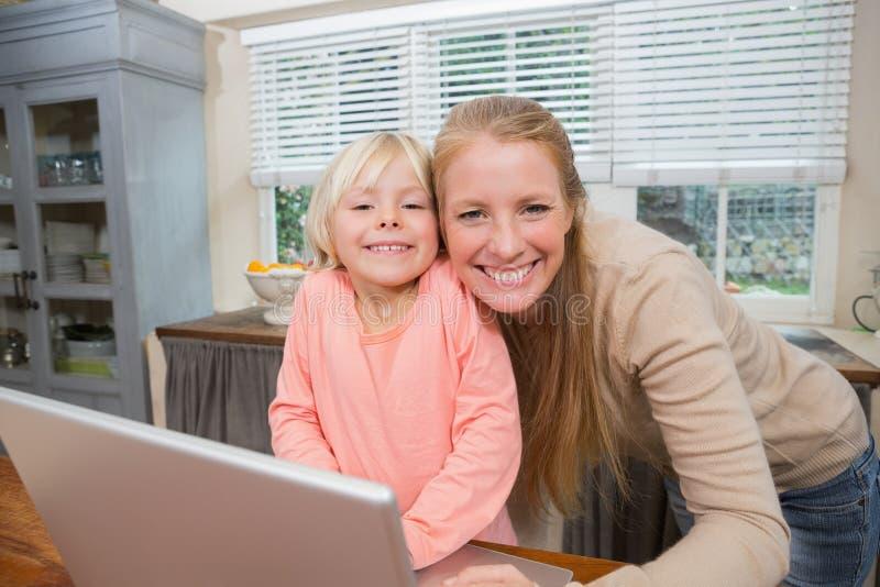 Χαριτωμένες κόρη και μητέρα που χαμογελούν στη κάμερα στοκ εικόνα με δικαίωμα ελεύθερης χρήσης