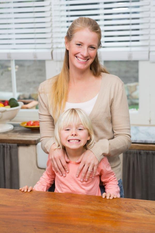 Χαριτωμένες κόρη και μητέρα που χαμογελούν στη κάμερα στοκ φωτογραφίες με δικαίωμα ελεύθερης χρήσης