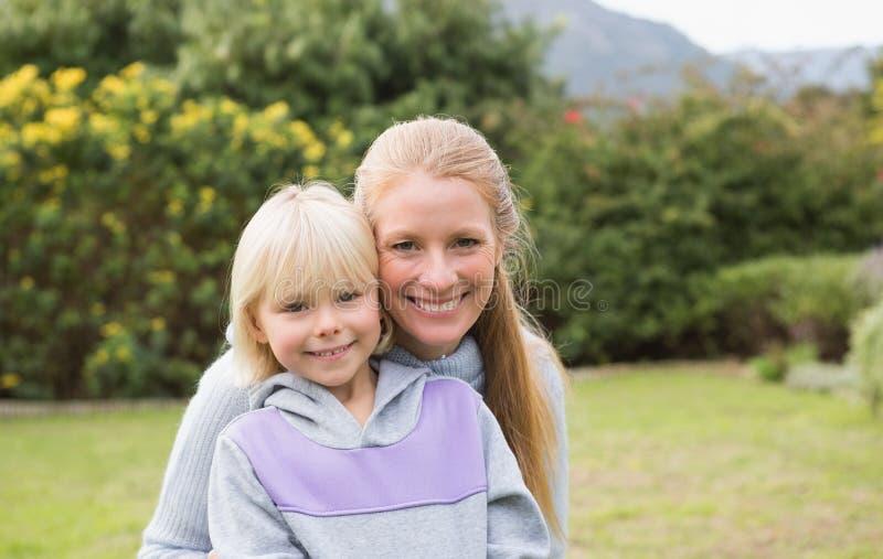 Χαριτωμένες κόρη και μητέρα που χαμογελούν στη κάμερα στοκ εικόνες