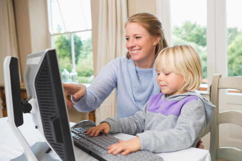 Χαριτωμένες κόρη και μητέρα που χρησιμοποιούν τον υπολογιστή στοκ φωτογραφία