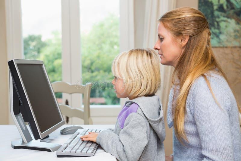 Χαριτωμένες κόρη και μητέρα που χρησιμοποιούν τον υπολογιστή στοκ φωτογραφία με δικαίωμα ελεύθερης χρήσης