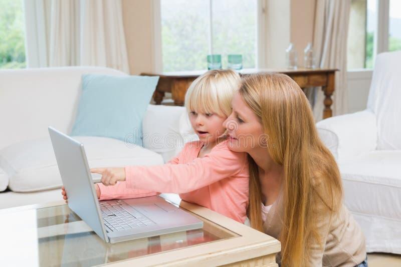 Χαριτωμένες κόρη και μητέρα που χρησιμοποιούν το lap-top στο τραπεζάκι σαλονιού στοκ φωτογραφία