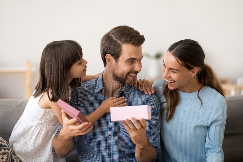 Χαριτωμένες κόρη και σύζυγος που συγχαίρουν το ευτυχές δώρο ανοίγματος πατέρων στοκ εικόνες
