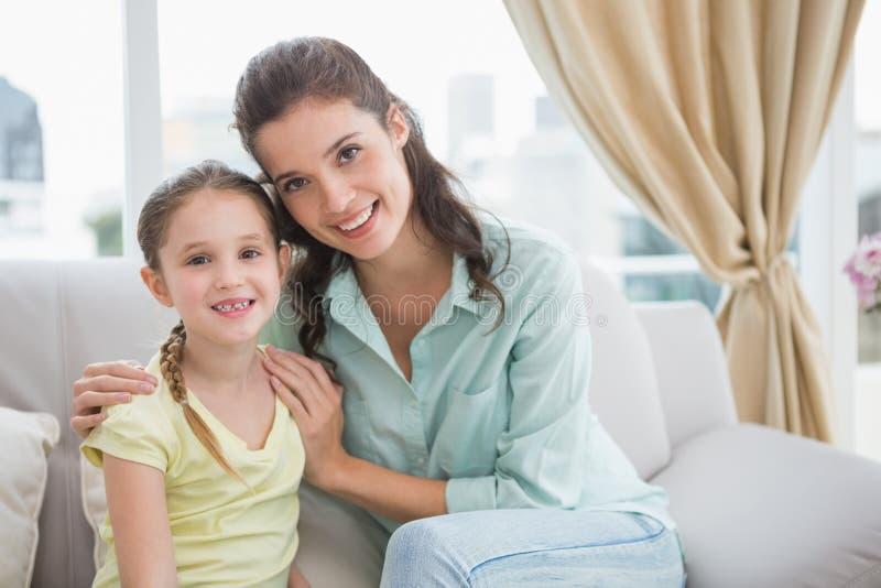 Χαριτωμένες μητέρα και κόρη που χαμογελούν στη κάμερα στοκ φωτογραφία με δικαίωμα ελεύθερης χρήσης