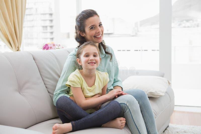 Χαριτωμένες μητέρα και κόρη στον καναπέ στοκ φωτογραφία
