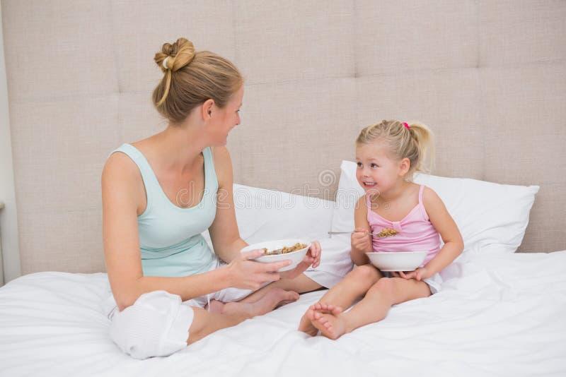 Χαριτωμένες μικρό κορίτσι και μητέρα στο κρεβάτι που τρώνε τα δημητριακά στοκ εικόνες με δικαίωμα ελεύθερης χρήσης