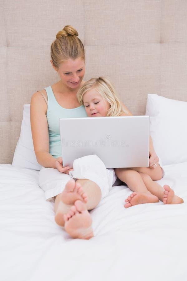Χαριτωμένες μικρό κορίτσι και μητέρα στο κρεβάτι που χρησιμοποιεί το lap-top στοκ εικόνες