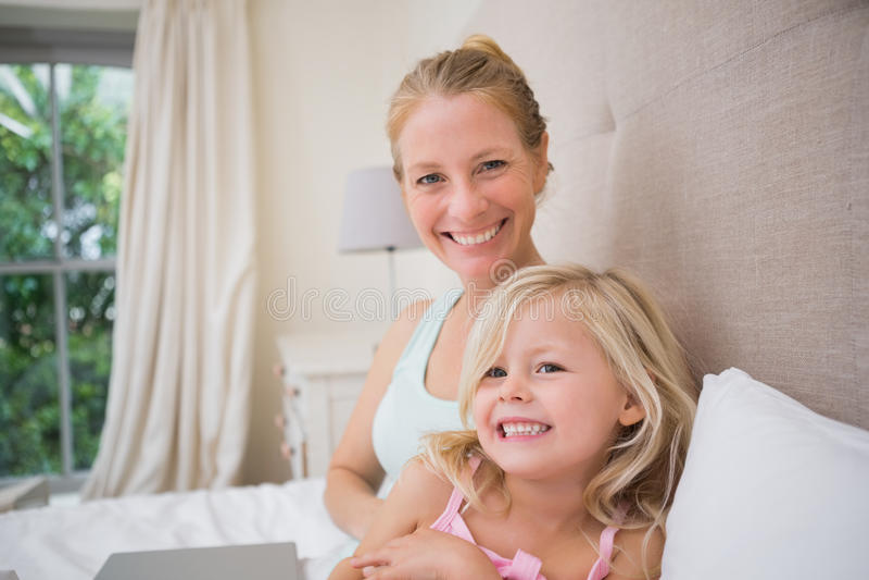 Χαριτωμένες μικρό κορίτσι και μητέρα στο κρεβάτι που χρησιμοποιεί το lap-top στοκ εικόνα με δικαίωμα ελεύθερης χρήσης