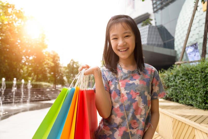 Χαριτωμένες τσάντες αγορών εκμετάλλευσης κοριτσιών αγορών στοκ εικόνα με δικαίωμα ελεύθερης χρήσης
