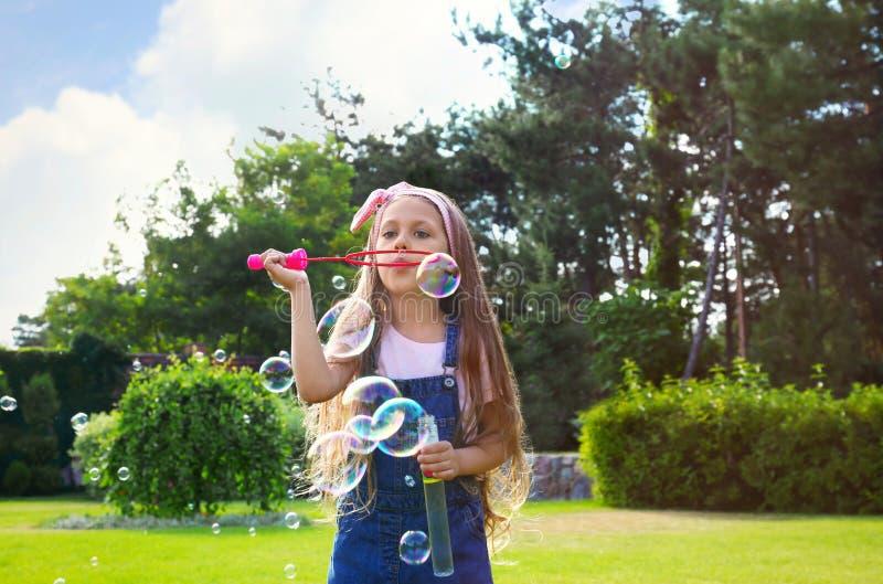 Χαριτωμένες φυσαλίδες σαπουνιών μικρών κοριτσιών φυσώντας στο πάρκο στοκ εικόνες