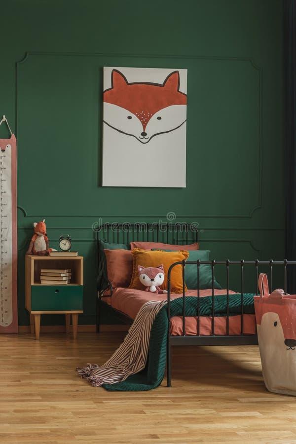 Χαριτωμένη ένωση αλεπούδων σε έναν σκούρο πράσινο τοίχο σε ένα εσωτερικό κρεβατοκάμαρων παιδιών με το κρεβάτι μετάλλων, τα πορτοκ στοκ φωτογραφίες με δικαίωμα ελεύθερης χρήσης