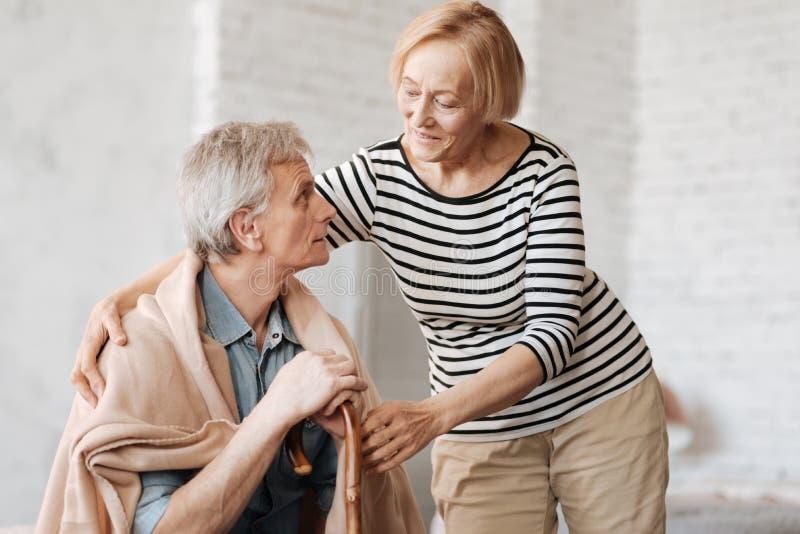 Χαριτωμένη αγαπώντας κυρία που φροντίζει το σύζυγό της στοκ φωτογραφίες
