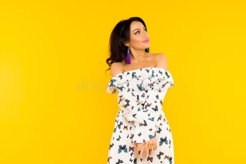 Χαριτωμένη ασιατική γυναίκα στο φόρεμα μεταξιού με τις πεταλούδες που θέτει στο κίτρινο υπόβαθρο στοκ φωτογραφία με δικαίωμα ελεύθερης χρήσης