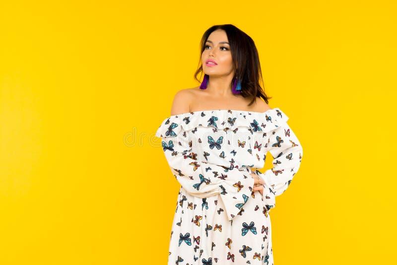 Χαριτωμένη ασιατική γυναίκα στο φόρεμα μεταξιού με τις πεταλούδες που θέτει στο κίτρινο υπόβαθρο στοκ φωτογραφία