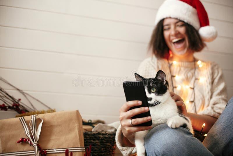 Χαριτωμένη γάτα που εξετάζει την τηλεφωνική οθόνη με τις αστείες συγκινήσεις και που κάθεται στα ευτυχή πόδια κοριτσιών στα φω'τα στοκ φωτογραφίες με δικαίωμα ελεύθερης χρήσης