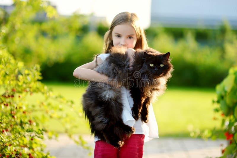 Χαριτωμένη γιγαντιαία μαύρη γάτα εκμετάλλευσης μικρών κοριτσιών στοκ εικόνες με δικαίωμα ελεύθερης χρήσης