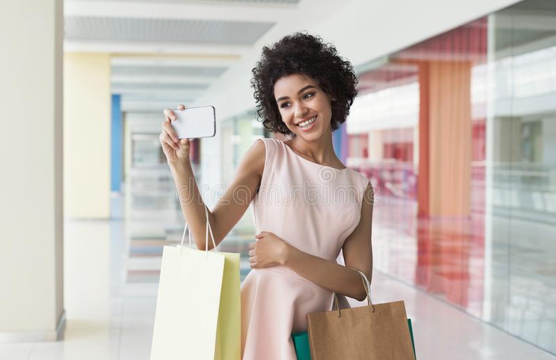 Χαριτωμένη γυναίκα αφροαμερικάνων που παίρνει selfie με τις τσάντες αγορών στοκ εικόνες με δικαίωμα ελεύθερης χρήσης