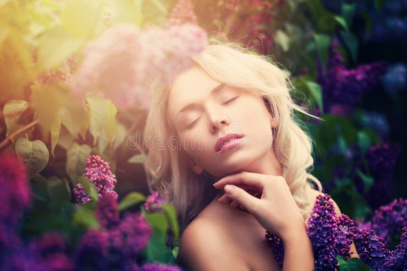 Χαριτωμένη γυναίκα με τα θερινά ελαφριά και ιώδη λουλούδια στοκ φωτογραφία με δικαίωμα ελεύθερης χρήσης