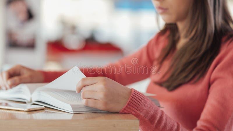 Χαριτωμένη γυναίκα που διαβάζει ένα βιβλίο στοκ φωτογραφίες