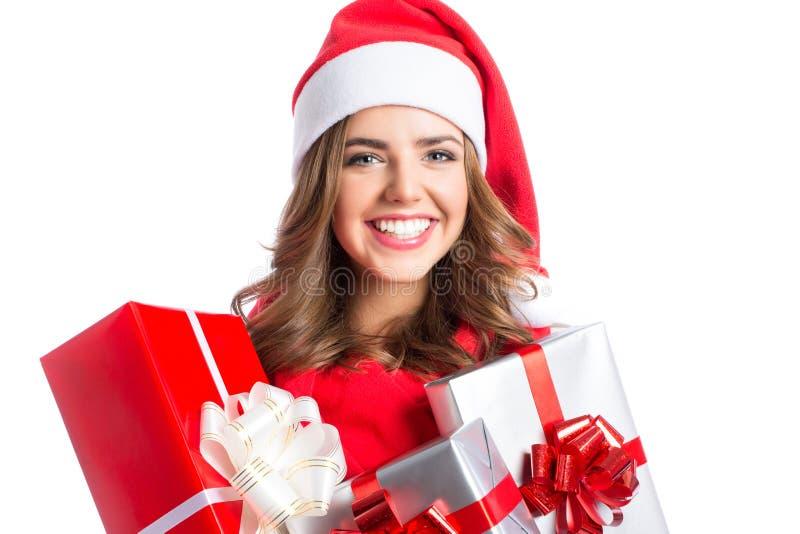 Χαριτωμένη γυναίκα που κρατά Χριστούγεννα και νέα δώρα έτους Κορίτσι Χριστουγέννων στο καπέλο santa με τα κιβώτια στοκ φωτογραφία