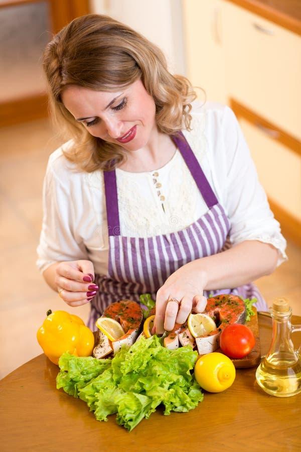 Χαριτωμένη γυναίκα που προετοιμάζει τα ψάρια στην κουζίνα στοκ φωτογραφίες με δικαίωμα ελεύθερης χρήσης