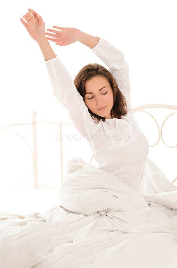 Χαριτωμένη γυναίκα που τεντώνεται μετά από τον ύπνο στοκ εικόνες