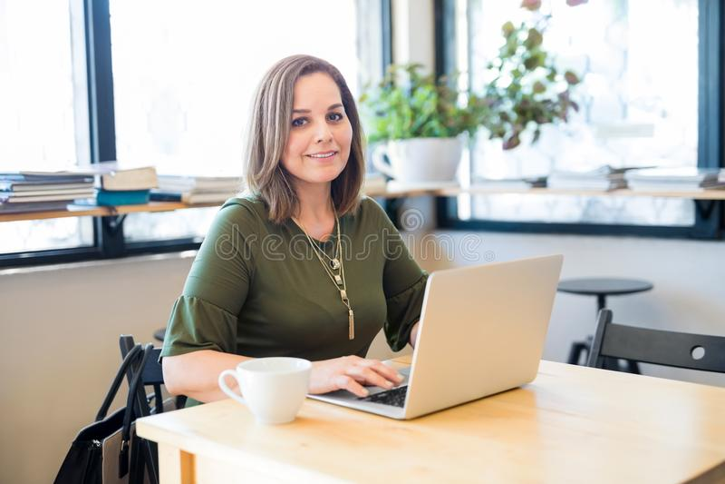 Χαριτωμένη γυναίκα στον καφέ με το lap-top στοκ εικόνες με δικαίωμα ελεύθερης χρήσης