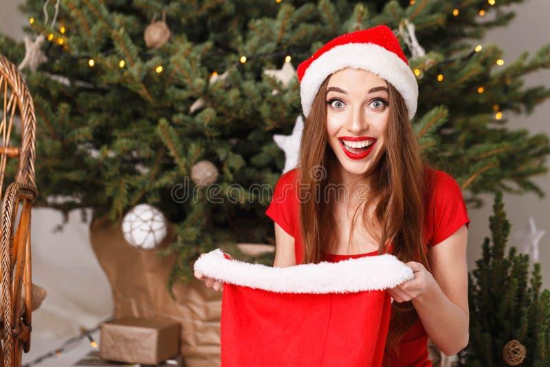 Χαριτωμένη γυναίκα Χριστουγέννων που φορά το καπέλο Santa που συγκλονίζεται από τα δώρα στοκ φωτογραφίες