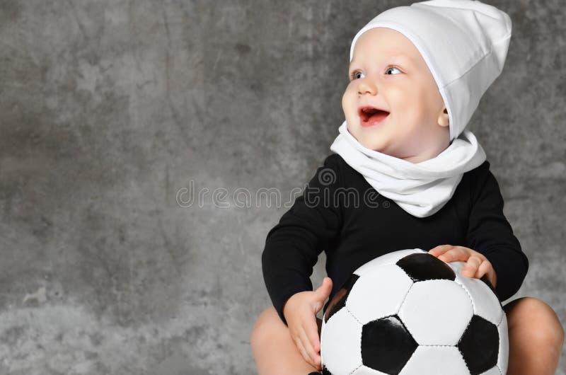 Χαριτωμένη εικόνα του μωρού που κρατά μια σφαίρα ποδοσφαίρου στοκ εικόνες με δικαίωμα ελεύθερης χρήσης