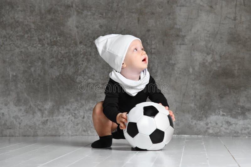 Χαριτωμένη εικόνα του μωρού που κρατά μια σφαίρα ποδοσφαίρου στοκ εικόνα με δικαίωμα ελεύθερης χρήσης