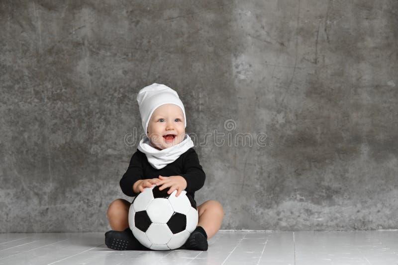 Χαριτωμένη εικόνα του μωρού που κρατά μια σφαίρα ποδοσφαίρου στοκ εικόνες