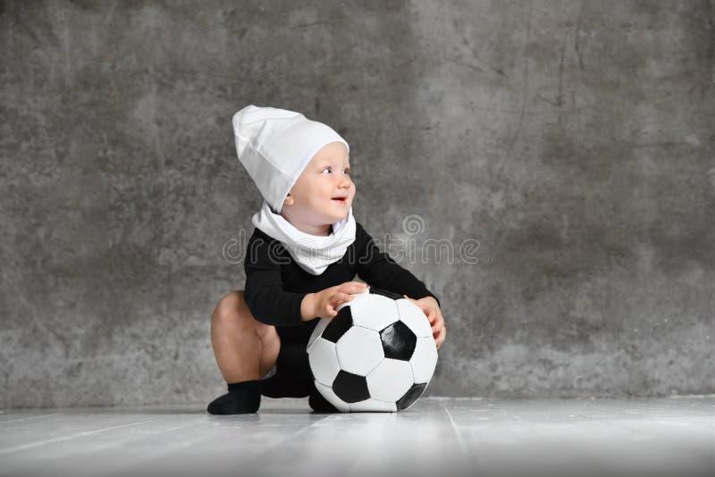 Χαριτωμένη εικόνα του μωρού που κρατά μια σφαίρα ποδοσφαίρου στοκ φωτογραφία