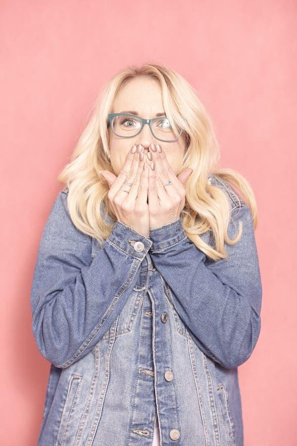 Χαριτωμένη ειλικρινής έκφραση, που κρύβει το surprisement της καλύπτοντας το στόμα της με τα χέρια στοκ φωτογραφία με δικαίωμα ελεύθερης χρήσης