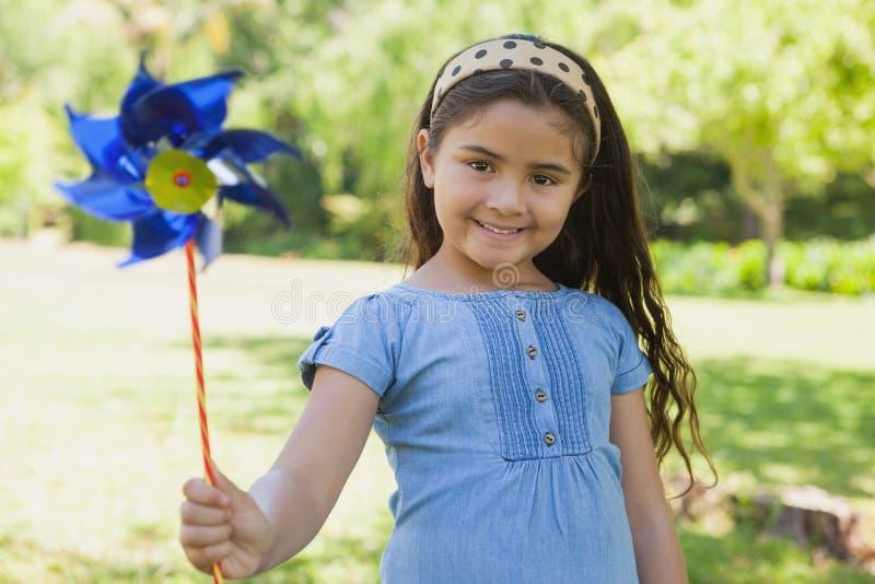 Χαριτωμένη εκμετάλλευση μικρών κοριτσιών pinwheel στο πάρκο στοκ εικόνες