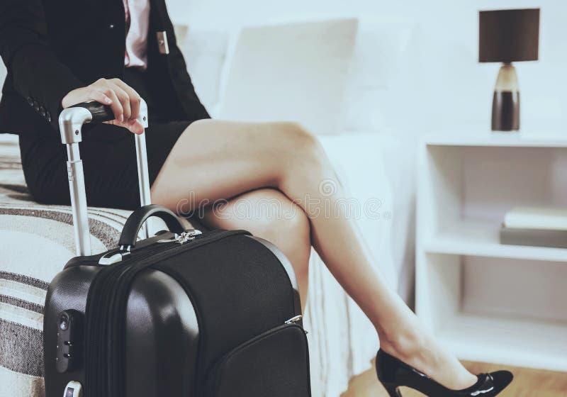 Χαριτωμένη επιχειρηματίας με τη συνεδρίαση βαλιτσών στο κρεβάτι στοκ φωτογραφίες