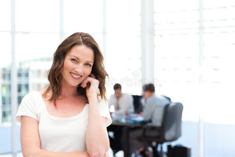 Χαριτωμένη επιχειρηματίας μπροστά από την ομαδική εργασία της στοκ φωτογραφία με δικαίωμα ελεύθερης χρήσης