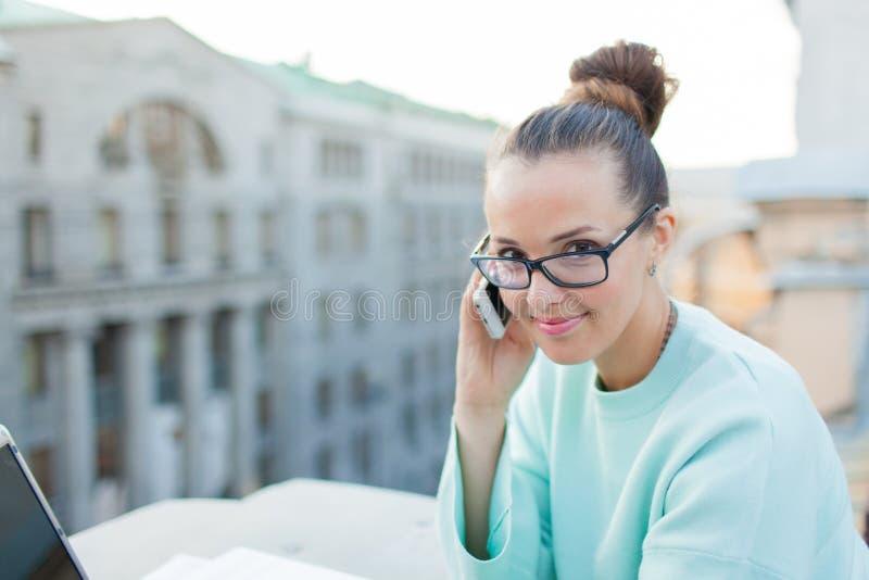 Χαριτωμένη επιχειρηματίας στα γυαλιά που μιλούν στο τηλέφωνο και που χαμογελούν στεμένος στη στέγη του σπιτιού στην παλαιά πόλη Δ στοκ φωτογραφίες