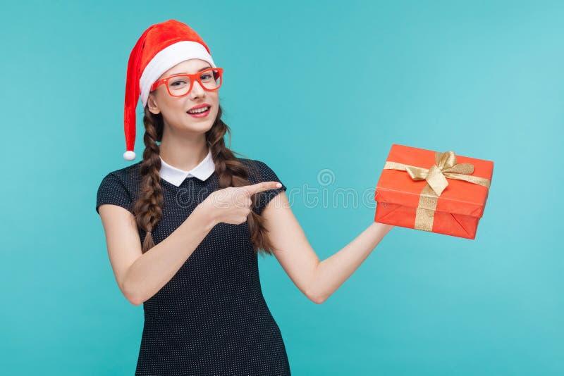 Χαριτωμένη επιχειρησιακή γυναίκα που δείχνει το δάχτυλο στο κιβώτιο και το χαμόγελο δώρων στοκ εικόνες