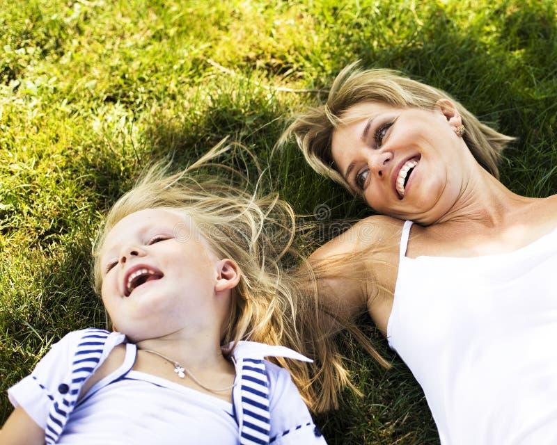 Χαριτωμένη ευτυχής οικογένεια στο πικ-νίκ που βάζει στην πράσινα μητέρα και το παιδί χλόης στοκ φωτογραφία με δικαίωμα ελεύθερης χρήσης