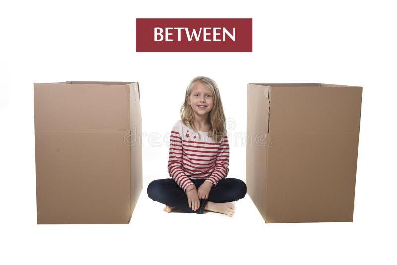 Χαριτωμένη και γλυκιά συνεδρίαση παιδιών ξανθών μαλλιών μεταξύ δύο κουτιών από χαρτόνι στοκ φωτογραφία με δικαίωμα ελεύθερης χρήσης