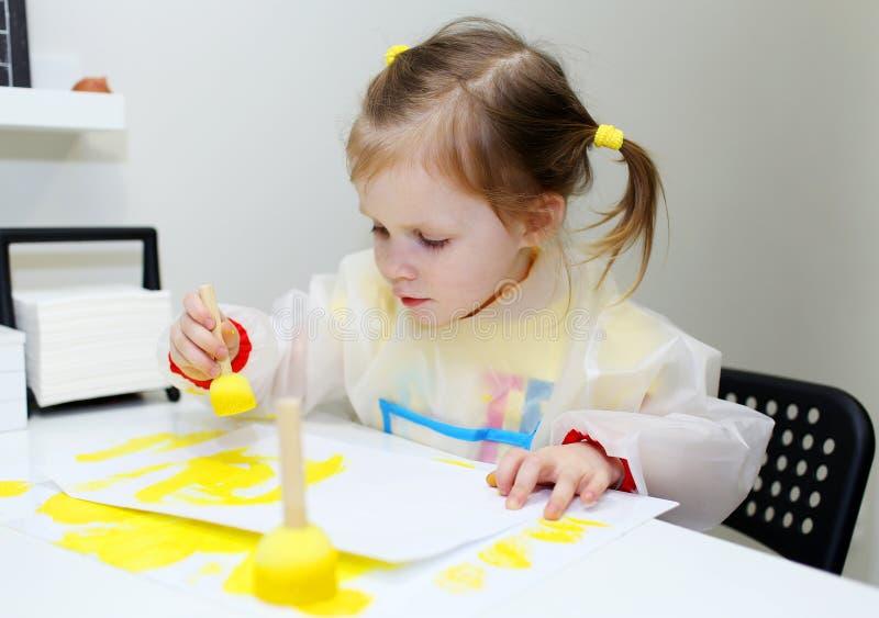 Χαριτωμένη καλή ζωγραφική μικρών κοριτσιών με τη βούρτσα αφρού στο σπίτι στοκ φωτογραφίες με δικαίωμα ελεύθερης χρήσης
