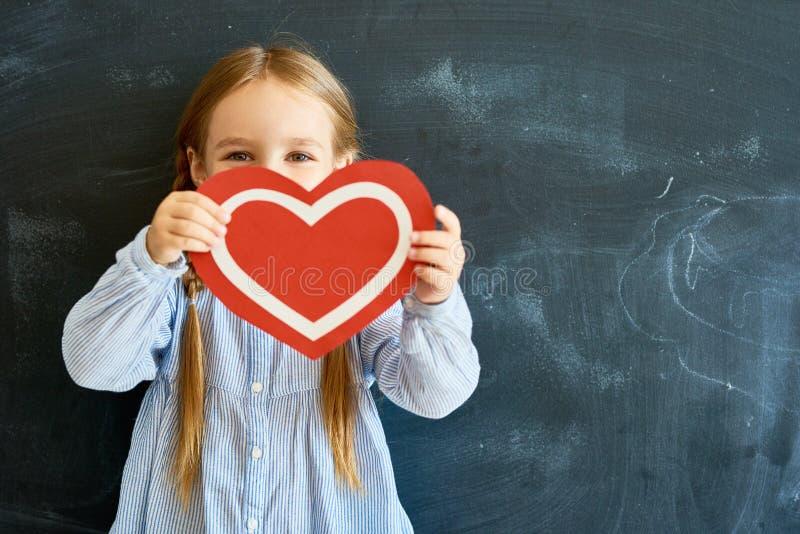 Χαριτωμένη καρδιά εγγράφου εκμετάλλευσης μικρών κοριτσιών στοκ εικόνα