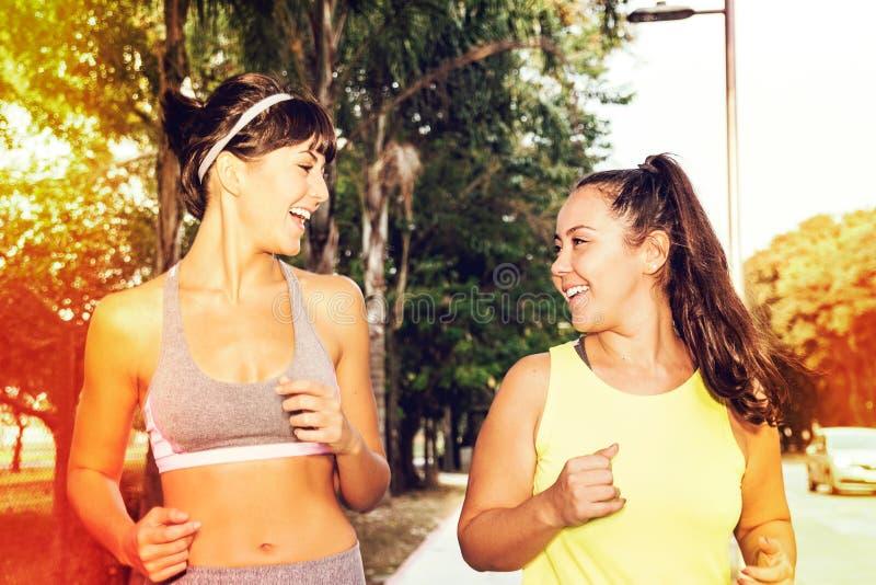 Χαριτωμένη καυκάσια γυναίκα και αρκετά ασιατικό κορίτσι που απολαμβάνουν ένα τρέξιμο outsid στοκ φωτογραφία με δικαίωμα ελεύθερης χρήσης
