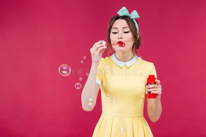 Χαριτωμένη καλή νέα γυναίκα στις κίτρινες φυσαλίδες σαπουνιών φορεμάτων φυσώντας στοκ εικόνα με δικαίωμα ελεύθερης χρήσης