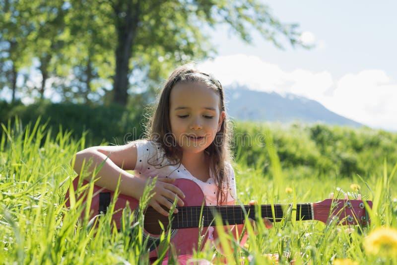 Χαριτωμένη κιθάρα παιχνιδιού κοριτσιών στον τομέα στοκ φωτογραφίες με δικαίωμα ελεύθερης χρήσης