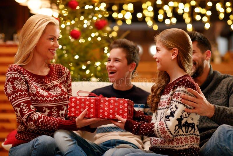 Χαριτωμένη κόρη που δίνει το δώρο Χριστουγέννων στη μητέρα στοκ φωτογραφίες