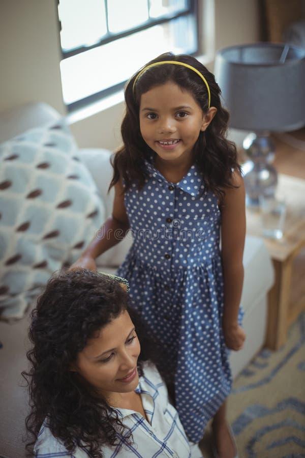 Χαριτωμένη κόρη που κτενίζει την τρίχα μητέρων στο καθιστικό στοκ φωτογραφίες