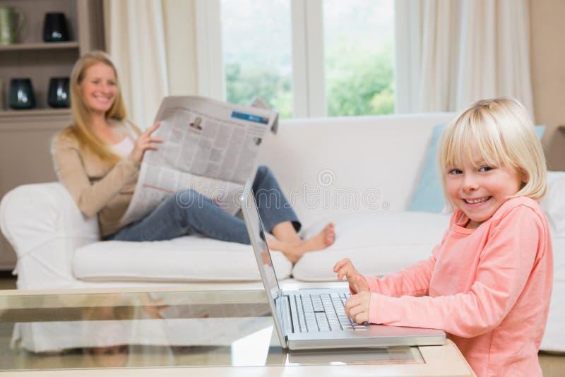 Χαριτωμένη κόρη που χρησιμοποιεί το lap-top στο τραπεζάκι σαλονιού στοκ φωτογραφίες με δικαίωμα ελεύθερης χρήσης