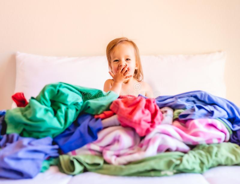 Χαριτωμένη, λατρευτή, χαμογελώντας, καυκάσια συνεδρίαση μωρών σε έναν σωρό του βρώμικου πλυντηρίου στο κρεβάτι στοκ εικόνες
