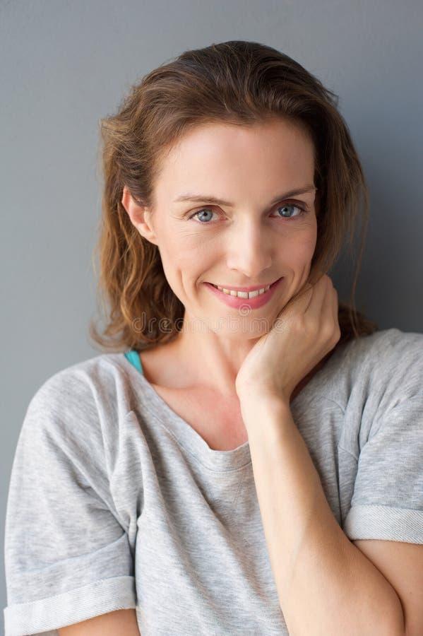 Χαριτωμένη μέση ενήλικη γυναίκα που χαλαρώνουν και που χαμογελά στοκ εικόνες